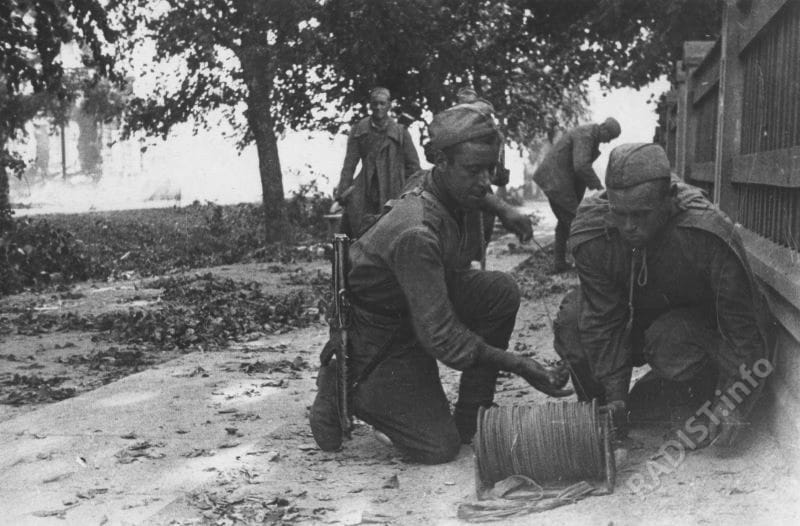 Советские связисты прокладывают линию связи во время уличных боев в Тарту. Эстония, август 1944 г.