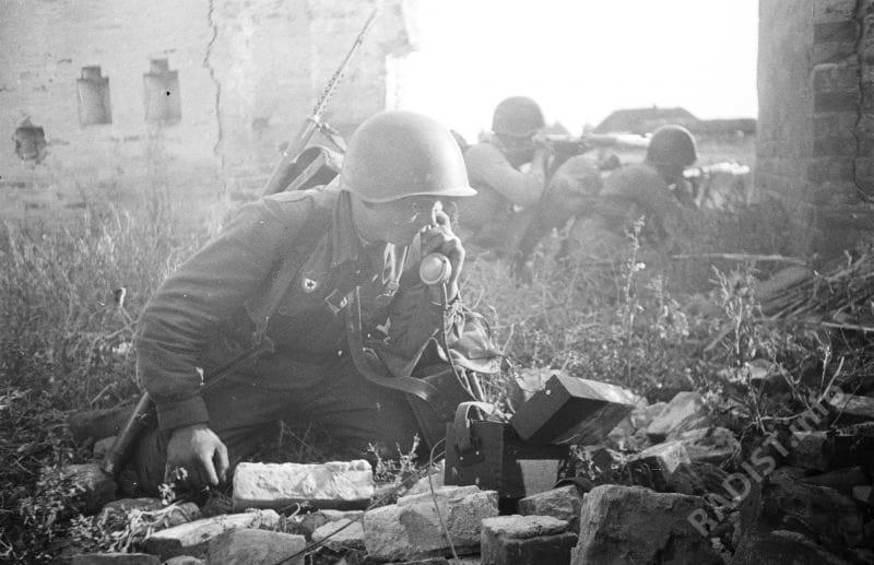 Связист гвардии рядовой Александр Егорович Ильченко из 73-го гвардейского стрелкового полка 25-й гвардейской стрелковой дивизии у полевого телефона во время уличных боев в районе Воронежа, 1944 г.