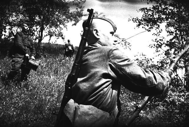 Связисты 3 части Калининского фронта прокладывают линию связи. На первом плане сержант Г.Л. Загребельный, 1942 г.