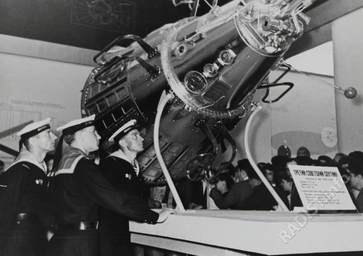 Военные моряки-радисты В. Тимченко, В. Андрусов и Н. Квачев посетили павильон Академии Наук СССР на Всесоюзной промышленной выставке, где экспонировался макет 3-го советского спутника. Моряки одними из первых приняли позывные